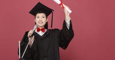 Mulher vestindo uma beca de formatura segura um diploma enquanto fala ao microfone.