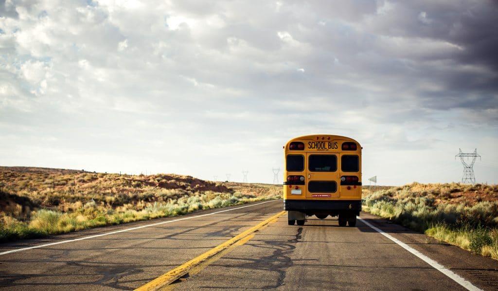 Ônibus amarelo escolar em uma das rodovias dos Estados Unidos. A rodovia está livre e tranquila.