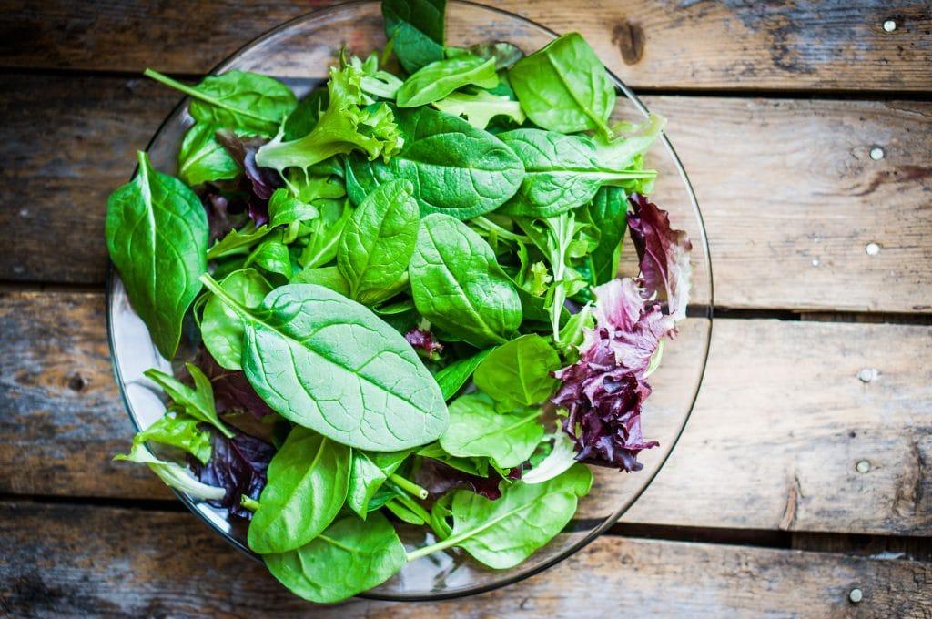 Salada em um recipiente de vidro em uma mesa de madeira