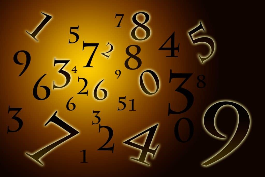 Vários números nas cores preto e com bordas em branco sobre um efeito de fundo dourado.