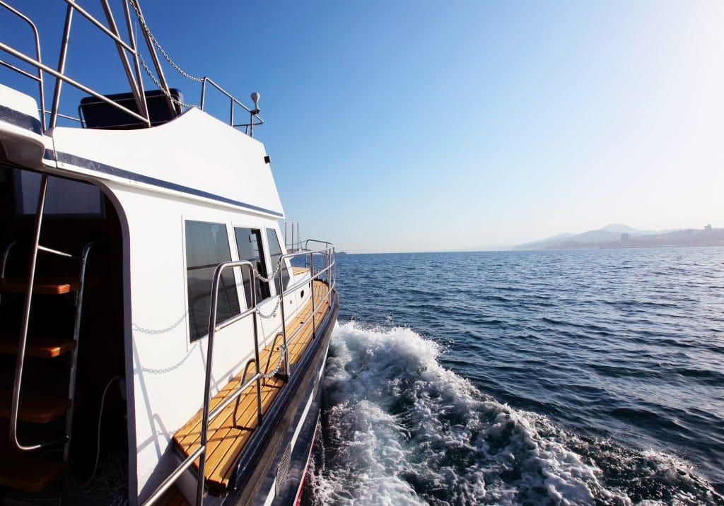 Barco branco navegando em alto mar. O céu está limpo e azul.