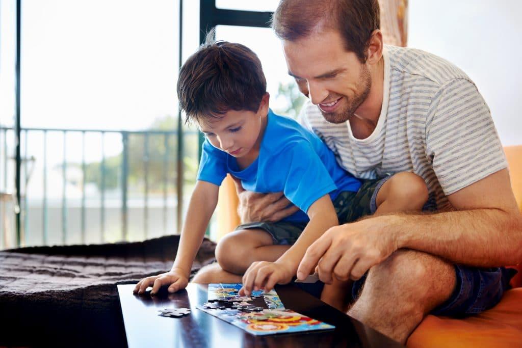 Pai e filho montando um quebra-cabeça. Eles estão na sala de estar, sentados em um sofá laranja.