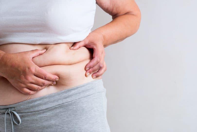 Mulher segurando dobrinhas da barriga