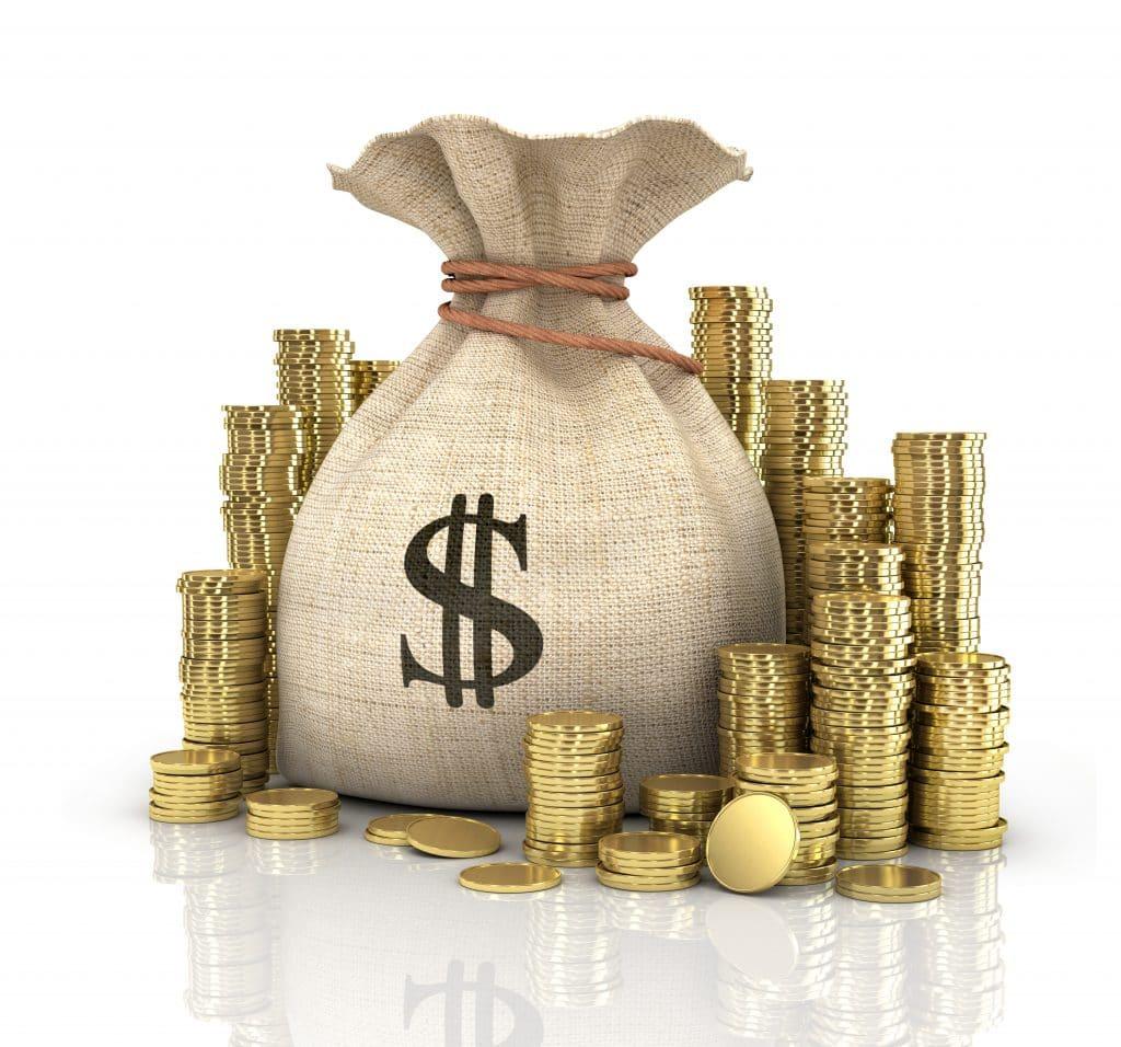 Saco de juta fechado. Ele possui o símbolo do cifrão pintado de preto. Ao lado deste saco, várias moedas douradas.