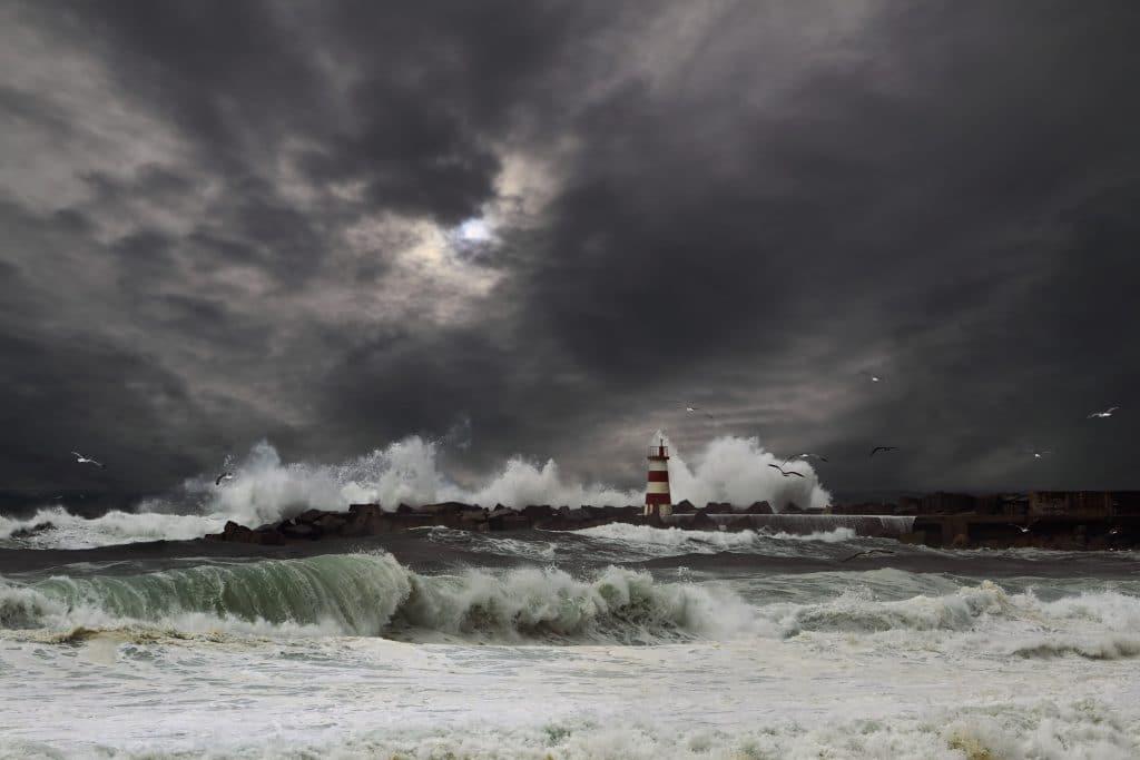 Tempestado em alto mar. Ondas gigantes sobre o farol de um porto. O céu está bem carregado e cinzento. O mar está muito agitado.