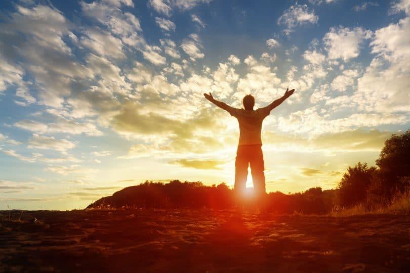 Silhueta de um homem com as mãos levantadas com por do sol e céu com nuvens ao fundo