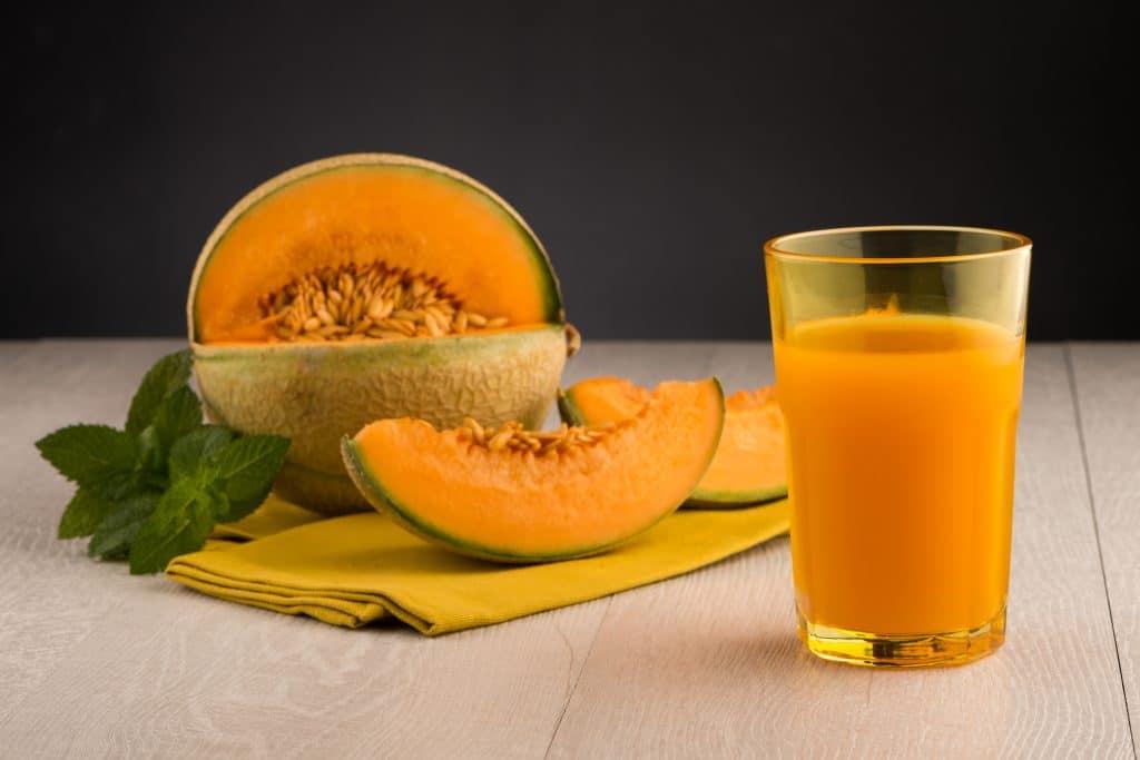 Suco de melão e hortelã para a gordura no fígado. Ele está sendo servido em um copo de vidro sobre a mesa de madeira. Ao lado um melão cortado e duas fatias da fruta com algumas folhas de hortelã.