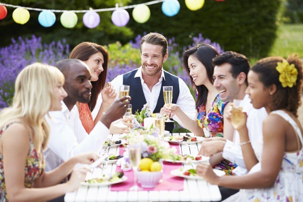 Grupo de amigos de várias etnias. Eles estão alegres e conversam bastante. Estão sentados à uma mesa cheia de guloseimas. É um ambiente descontraído.