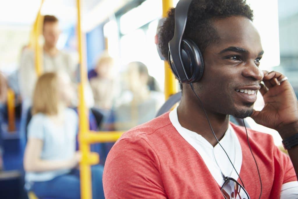 Homem negro dentro de um ônibus. Ele está sentado, vestindo uma blusa laranja sobre uma camiseta branca. Ela está com fone de ouvido, ouvindo uma música.