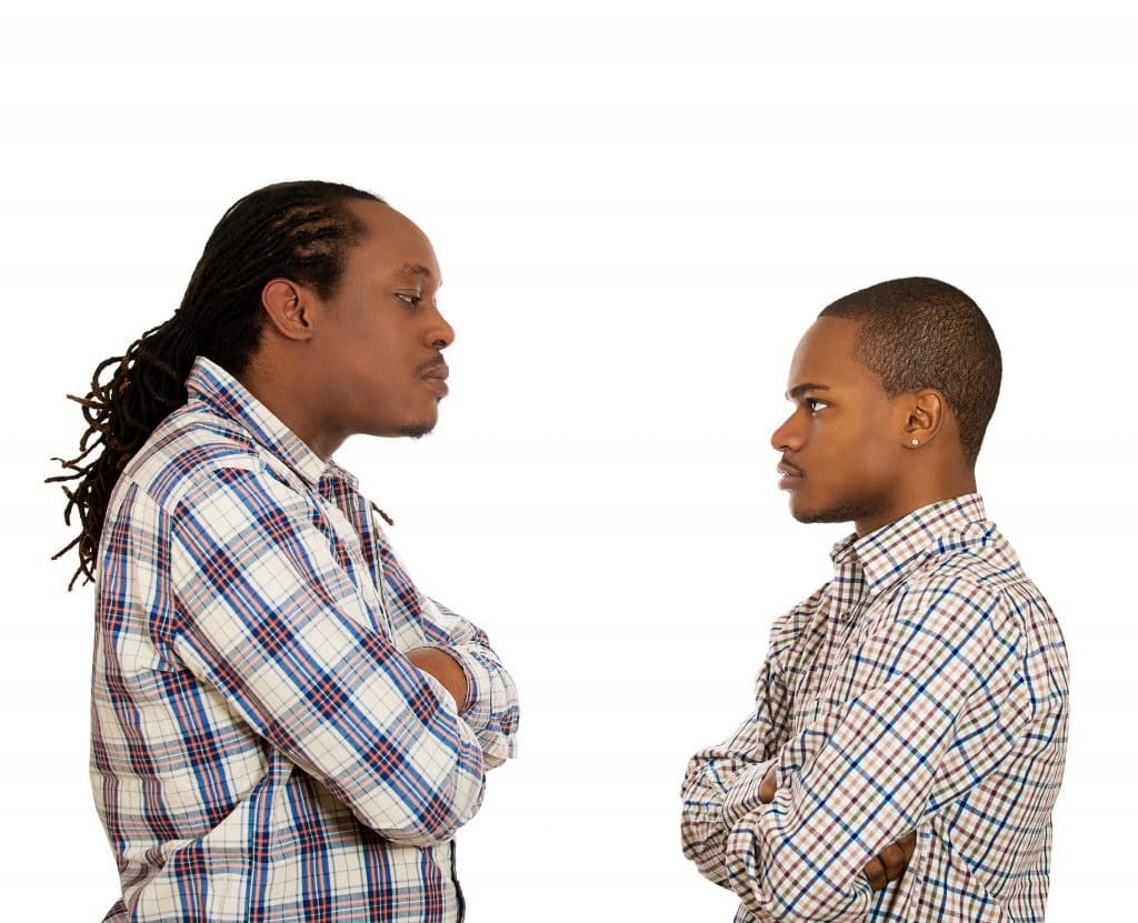 Dois homems negros, um de frente para o outro. Ambos estão se encarando e com ar de desprezo. Um é mais alto e possui cabelos longos o outro tem pouco cabelo. Ambos vestem camisa xadrez.