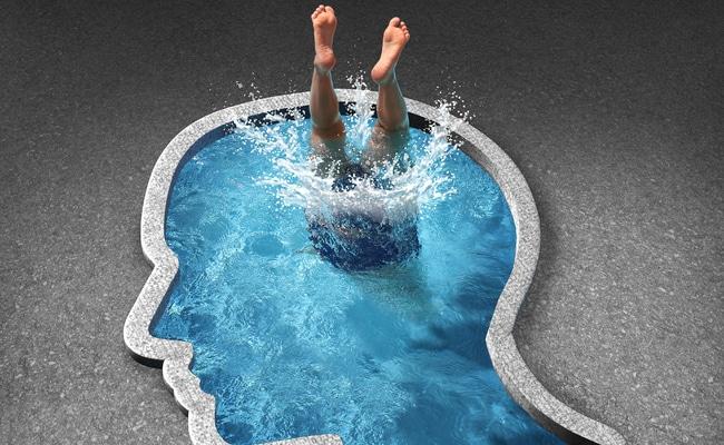 Pessoa mergulhando em piscina com formato de silhueta de uma cabeça humana.