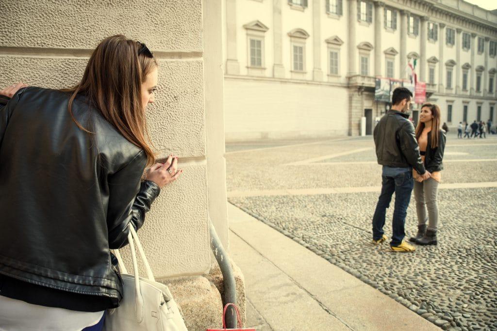 Ex-namorada espionando o seu ex-namorado que já está com outra namorada. Eles estão no centro de uma praça de mãos dadas, um olhando de frente para o outro. Está outono e ambos vestem jaqueta de couro preta.
