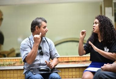 Homem se comunica com menina através da linguagem brasileira de sinais (libras).
