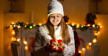 Mulher segurando presente de natal em casa enfeitada com luzes