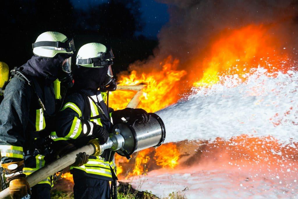 Dois bombeiros masculinos segurando um esguicho de água. Eles estão apagando um fogo.