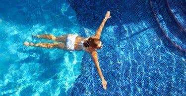 Mulher de biquíni branco nadando na piscina.