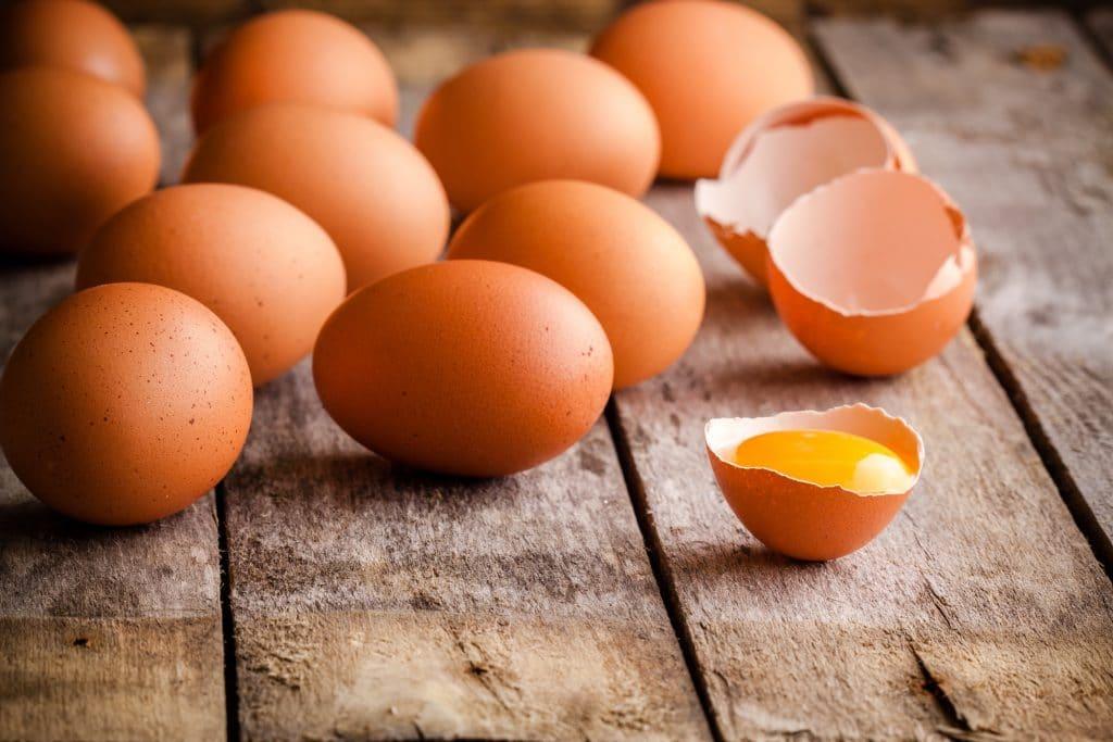 Dez ovos vermelhos inteiros e um ovo já quebrado com uma gema bem amarela. Eles estão sobre uma mesa de madeira.