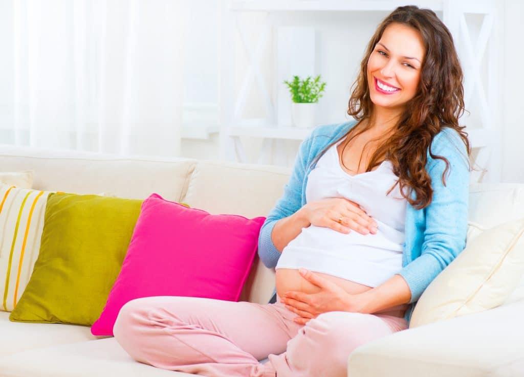 Mulher grávida, de cabelos longos e feliz. Ela está sentada em um sofá branco com almofadas coloridas, rosa, dourada e listrada. Ela usa uma calça rosa, regata branca e sueter azul.