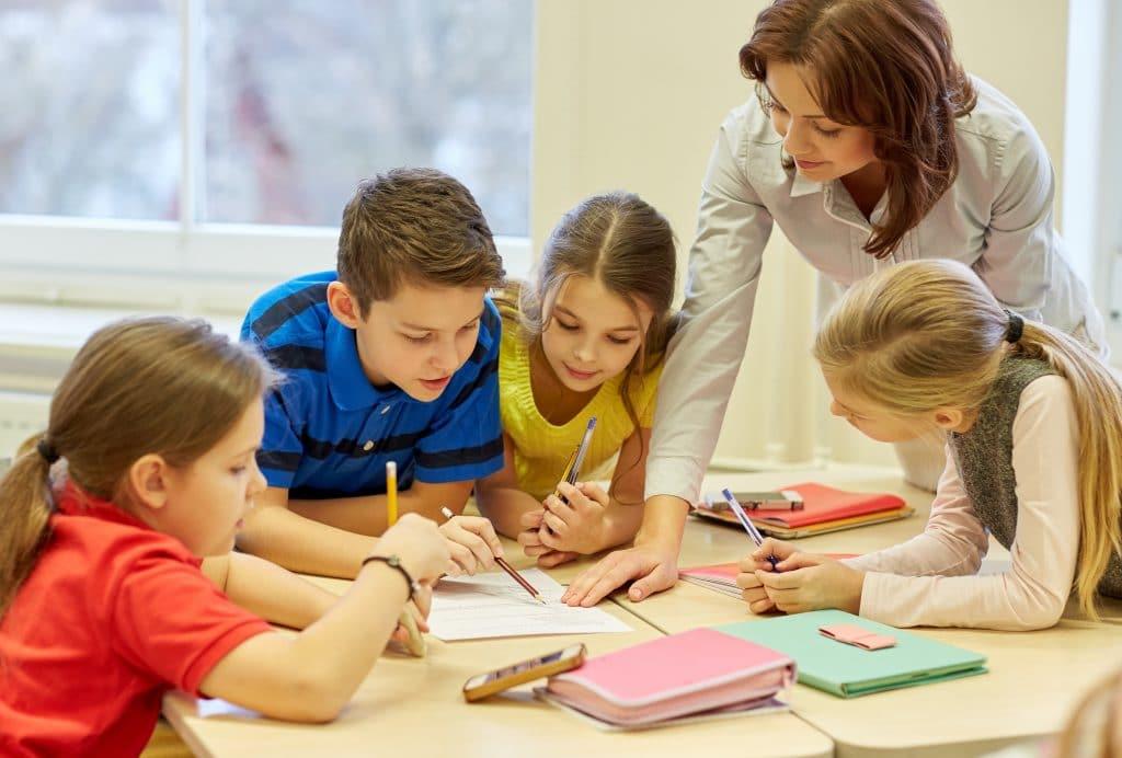 Uma mulher ajudando várias crianças (menino e meninas) a estudarem. Todas elas estão segurando uma caneta ou lápis e estão debruçadas sobre uma mesa de estudos, cheia de livros e cadernos.