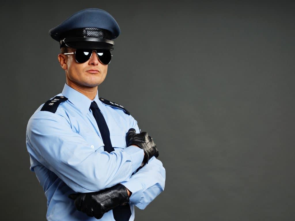 Imagem de policial masculino, uniformizado, usando uma camisa azul claro, gravata, luvas, boina e óculos pretos.