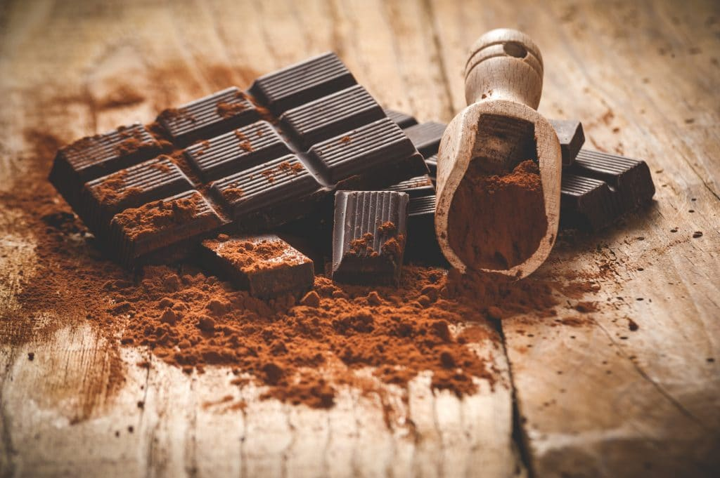 Tablete de chocolate escuro sobre uma mesa de madeira em estilo vintage.