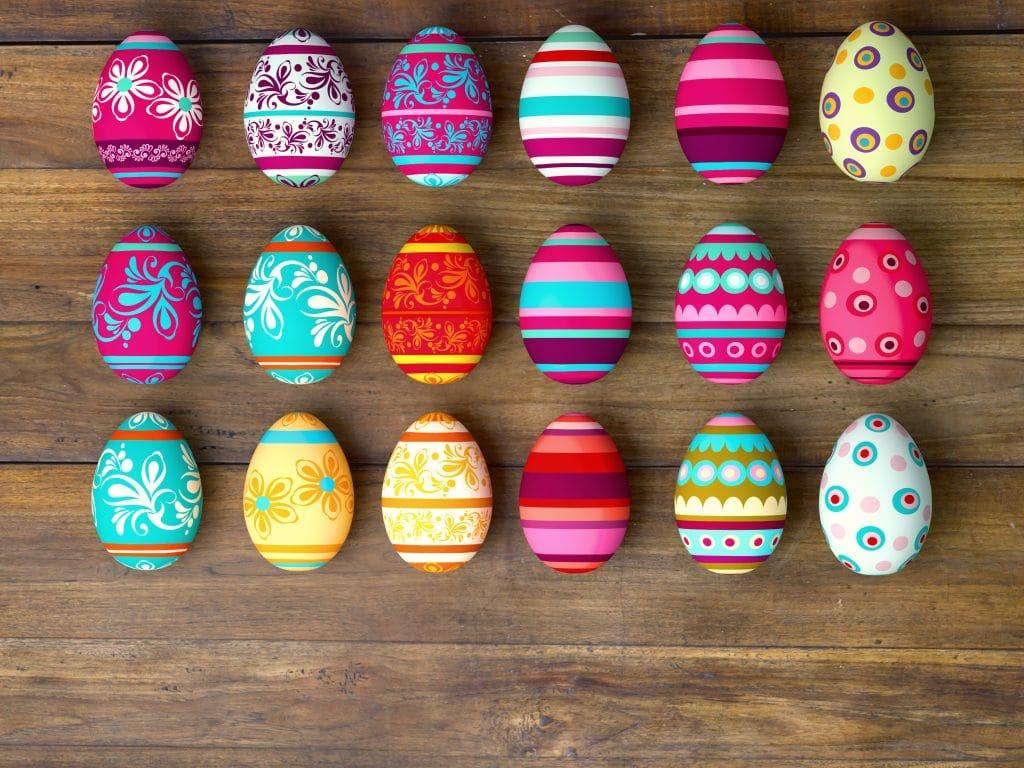 Dezoito ovos de páscoa pintados de formas e cores diferentes. Eles são alegres e estão dispostos sobre uma mesa de madeira marrom escura.