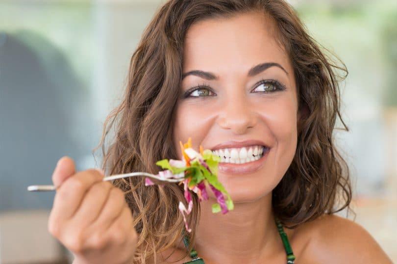 Mulher segurando um garfo com salada