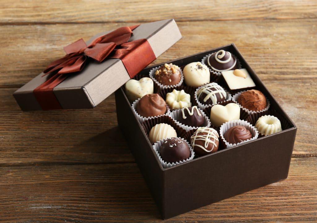 Caixa de presente feita de papelão com um laço grande na cor vermelho. A caixa está aberta e dentro dela vários bombons de chocolate de sabores variados.