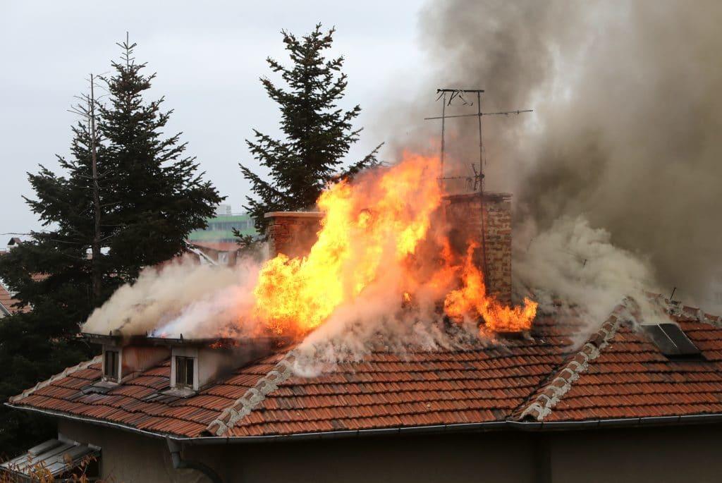 Uma grande casa pegando fogo. O fogo atingiu o teto e está saindo pelo telhado. Há muita fumaça no local.