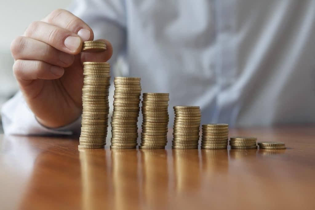 Várias moedas douradas sobre uma mesa de madeira. Uma mão masculina está colocando mais moedas sobre um dos montes de moedas.