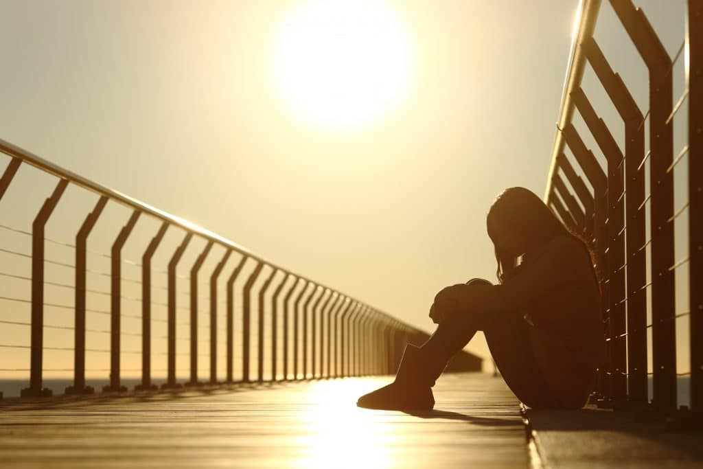 Imagem de uma mulher triste e cabisbaixa sentada sobre uma passarela. Ao fundo uma forte luz solar.