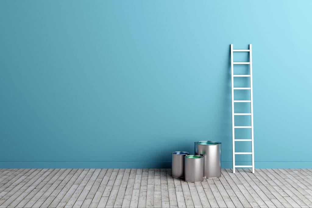 Escada branca encostada em uma parede pintada na cor azul piscina. Ao lado da escada três baldes de alumínio.