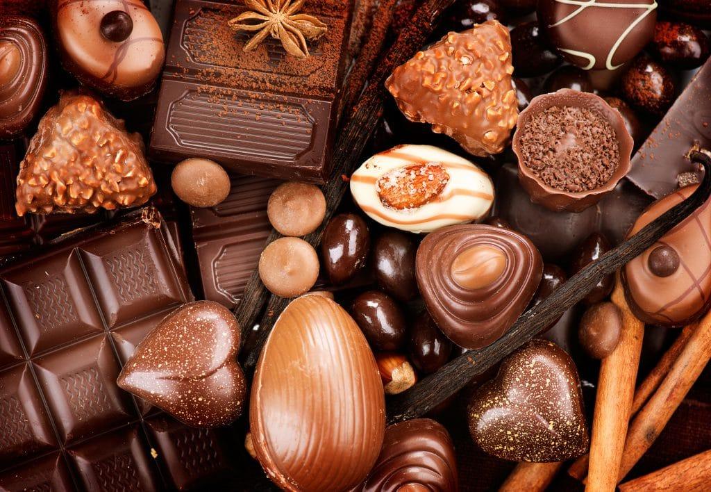Vários tipos de chocolate em diversos formatos: em barra, em ovos de pásgoa, em bombons, em corações. Estão todos juntos dispostos sobre uma mesa decorada com canela em pau.