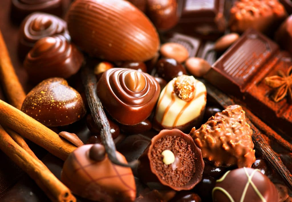 Vários tipos de bombons sortidos. São bombons de chocolate ao leite, de chocolate branco, meio amargo e amargo.