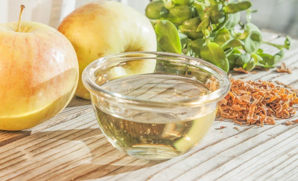 Vinagre de maçã amarelo em uma tigela de vidro. Ele está sobre uma mesa entre maçãs e ervas.