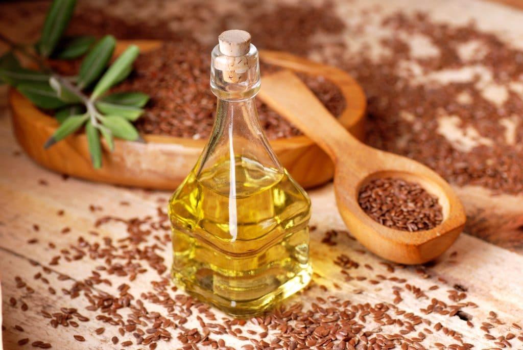 Semente de linhaça dentro de um recipiente de madeira. Ao lado uma colher também de madeira com um pouco de semente e um garrafa de vidro de óleo.