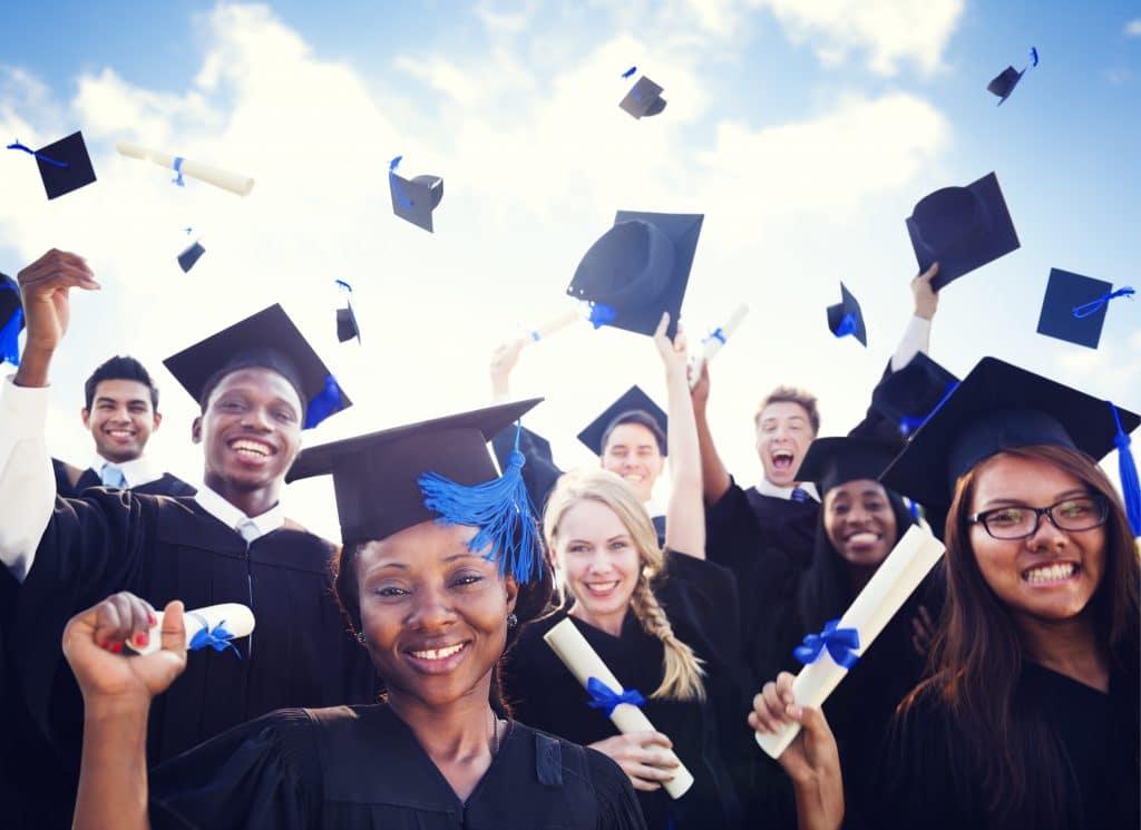Vários alunos em ritmo de festa, pois estão se formando. Eles usam beca e estão jogando o capelo para cima. São negros, brancos e japoneses, segurando em suas mãos o diploma.
