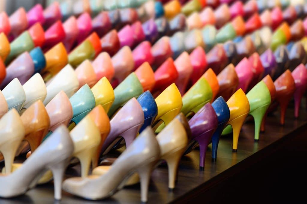 Vários sapatos feminino e de salto alto e todos de cores diferentes. É uma foto bem colorida e repleta de sapatos.