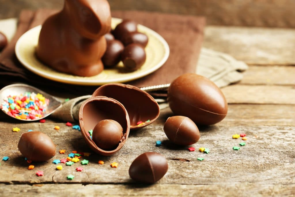Ovos de páscoa de chocolate de vários tamos. Alguns estão inteiros, outros pela metade. Ao fundo um prato com alguns ovinhos e um coelho feito de chocolate.