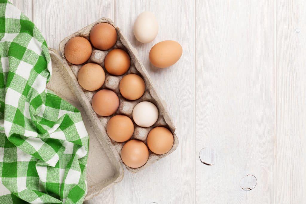 Caixa de ovos vermelhos aberta. Em uma das partes da caixa temos uma toalha quadriculada nas cores verde e branco. A caixa está sobre uma mesa de mandeira branca.