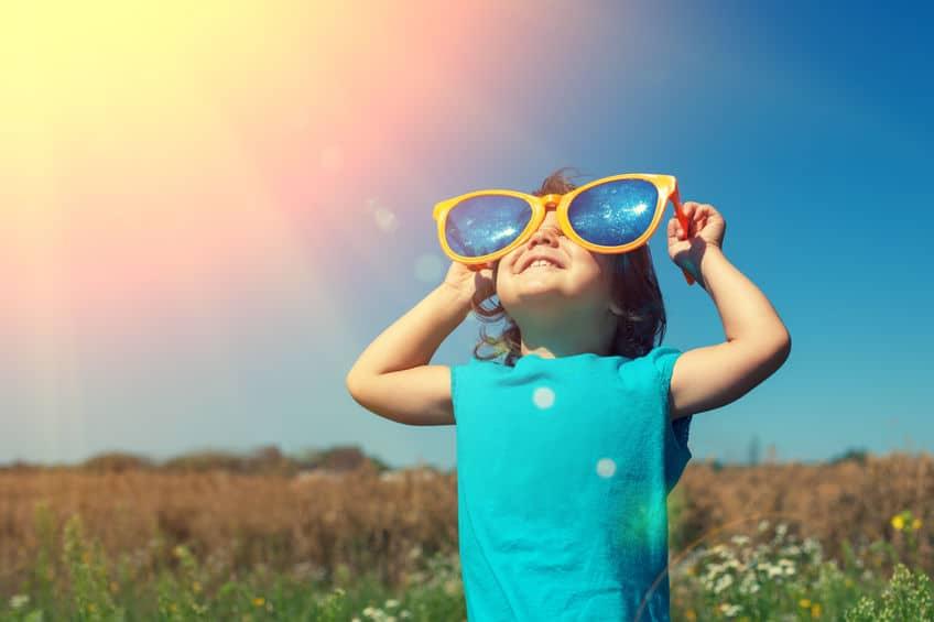 Menina encarando o Sol.