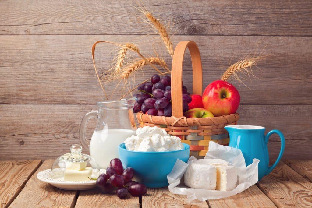 Cesta de vime de café da manhã completa com uvas, maças e trigo. Ao lado da cesta uma jarra de leite, uma de café, queijo frescal cortado, um cacho de uva e um pote com manteiga em pedaços.