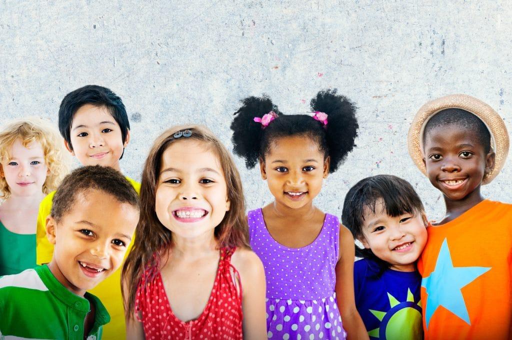 Muitas crianças de várias raças e nacionalidades. Todas elas estão felizes e sorrindo.
