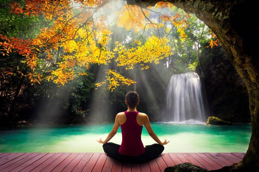 Mulher em posição de meditação. Ela está de frente para uma cascata de cachoeira sob uma árvore bem bonita e frondosa.