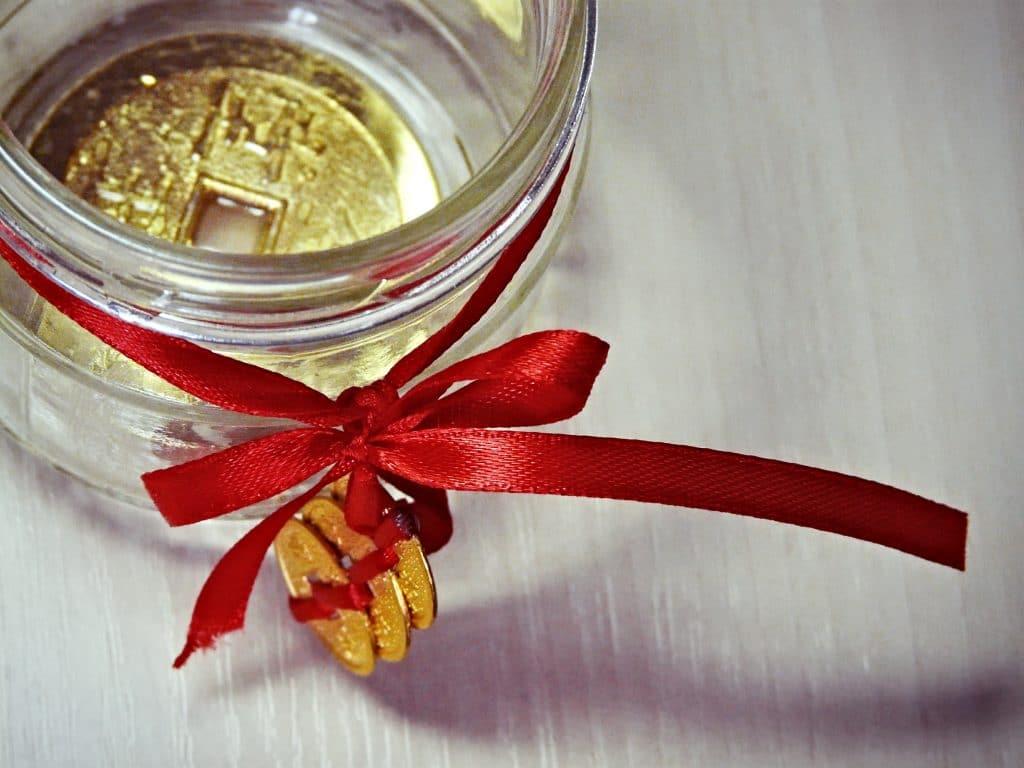 Talismã feito de moeda para Feng Shui. A moeda está armazenada em um recipiente de vidro decorado com um laço de fita vermelho com três moedas douradas penduradas.