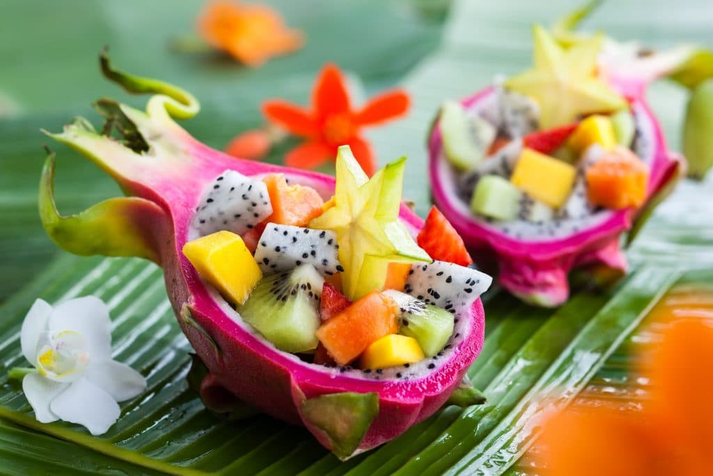 Salada de frutas bem saborosa servida dentro da fruta pitaya.