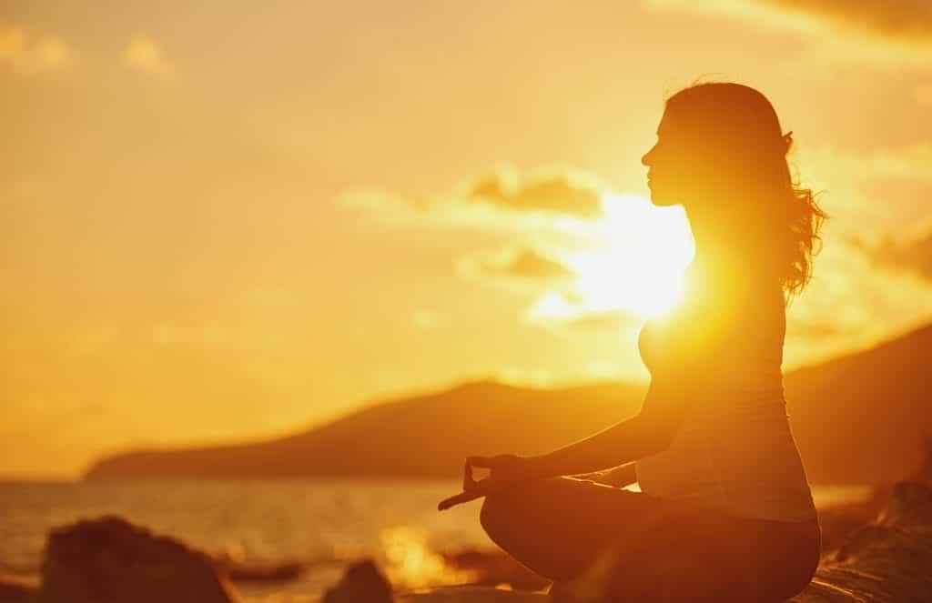 Mulher grávida praticando ioga, sentada em posição de lótus na praia e apreciando o pôr do sol.