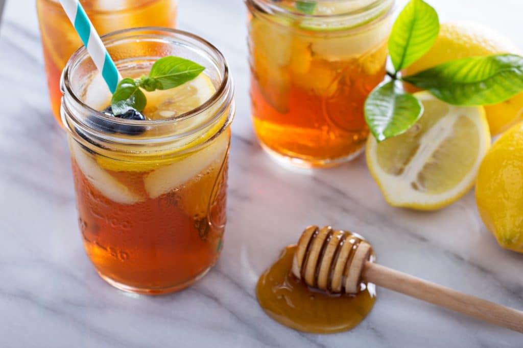 Suco de laranja com própolis e limão. Ele está sendo servido em canecas de vidro. Estão decorados com limão em pedaços e folha do limão. Ao lado temos uma colher de madeira contador de gotas de mel.
