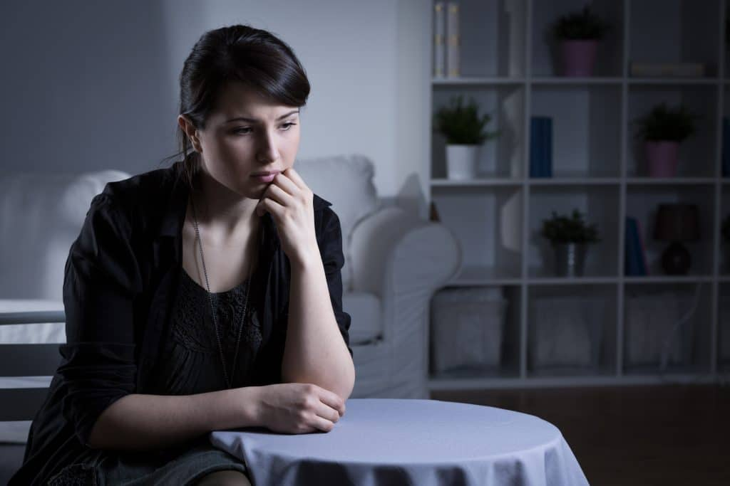 Mulher sentada. Ela está com os braços apoiados sobre uma mesa redonda com toalha branca. Ela está triste e deprimida.
