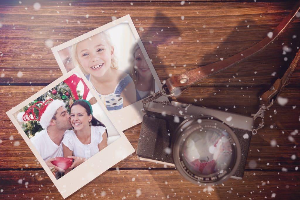 Painel de madeira com fotos da família e do casal afixadas. Ao lado uma câmera fotográfica analógica.